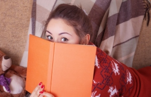 Cute girl on the sofa with a book